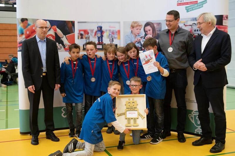 """Das Team """"Robogang VGS"""" der Von-Galen-Schule in Oeding belegte Platz 1 der Grundschulen in der Kategorie Robot-Game. Den Preis überreicht der Parlamentarische Staatssekretär Klaus Kaiser (links). Foto: zdi"""