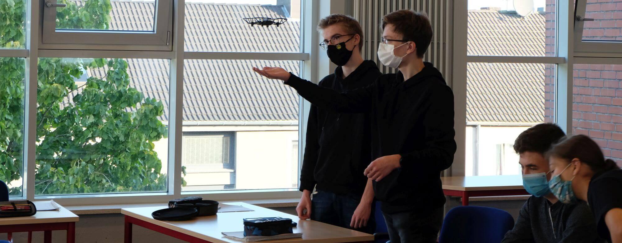 Zwei Teilnehmer mit fliegender Drohne bei einem Drohnen-Workshop