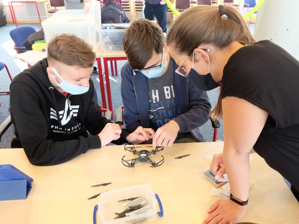 Schüler beim Reparieren einer Drohne mit einer Trainerin von brickobotik